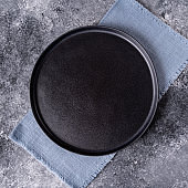 Black plate on blue napkin on a wooden table, top view, place for a menu or recipe.