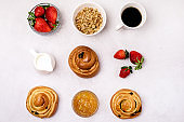Tasty Breakfast Freshly Baked Buns with Raisins and Cinnamon Cup of Black Coffee Cream Ripe Strawberry and Orange Jam in Glass Bowl Top View Flat Lay Muesli