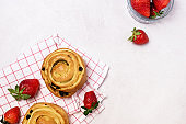 Freshly Baked Buns with Raisins and Cinnamon Decorated with Strawberry on Napkin Light Gray Background Horizontal Sweet Homemade Pastry Swedish Dessert