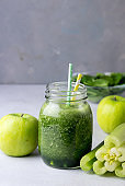 Glass Jar of Healthy Green Smoothie Detox Drink wirh Green Apple Celery and Raw Spinach Diet Beverage Vertical