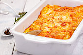 Potato gratin in white casserole dish on wooden rustic table. Close up