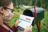Woman in protective face mask sending or receiving letter with voting ballot near a mailbox near her house