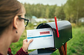 Woman sending or receiving letter with voting ballot near a mailbox near her house