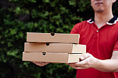 Pizza delivery boy holding pizza boxes in house garden in front of door with copy space