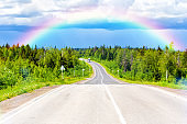 Bright rainbow over the highway and summer forest. After a thunderstorm