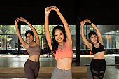 Female fitness women having a Latin dancing class together in gym studio. Group of young sportive women doing putting hands up in the air. Fitness and teamwork in Asia concept