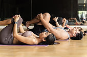 Group of Asian women and man doing pilates lying on yoga mats in aerobics class. Young sporty people stretching legs on the floor in gym studio.