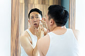 Puzzled Asian man checking acne problems while looking in mirror