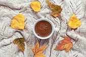 A cup of fresh coffee on knitted plaid, yellow autumnal leaves decoration. Autumn holiday concept