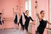 Small group of teenage girls practicing classical ballet in dancing studio