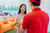 Asian businesswoman receiving pizza delivery at office