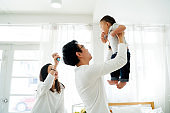 Asian father and mother as married couple lifts their own son up and flies up in the air with laughter and happiness. He is raised up with excitement. Parenthood in Asia concept