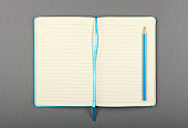 Open blue notebook with pencil over grey