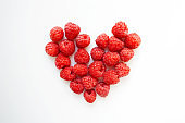 Juicy raspberries heart shaped composition
