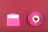 Pink paper letter envelope and coffee cup