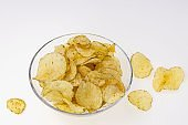 Close up view of crunchy potato chips in glass bowl on white background. Food and drinks beautiful backgrounds.
