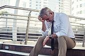 Depressed senior businessman in city