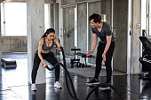 woman battle rope exercise with coach in gym