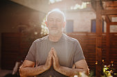 Active senior man standing with his palms together in meditation