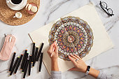 Woman drawing and coloring mandala in sketchbooks with colorful markers while having a breakfast