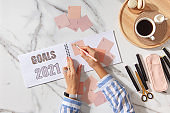 Woman writing personal New Year goals list for 2021 on coral colored notepads while drinking coffee. Marble background