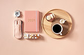 Top view of coral colored diary 2021, pen case, gift boxes, o'clock and coffee with milk and macaron