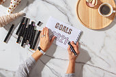 Woman writing personal New Year goals list for 2021 on notepads while drinking coffee