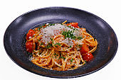 spaghetti pasta with rich creamy tomato sauce and grated parmeesan cheese in a serving bowl