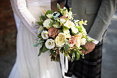 Couple holding a wedding bouquet.