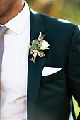 Men's accessories, perfume, boutonniere, gold rings, watches and leather shoes of the groom.