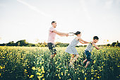 Father, son and daughter playing in the rape fields