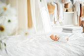 Funny little newborn baby in white bodysuit sleeps