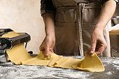 Woman preparing dough with pasta maker machine at grey table, closeup
