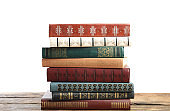 Stack of old vintage books on wooden table against white background