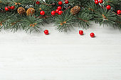 Composition with fir branches and berries on white wooden background, space for text. Winter holidays