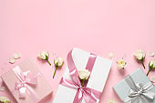 Elegant gift boxes and beautiful flowers on pink background, flat lay. Space for text