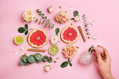 Top view of woman spraying perfume on pink background, flowers and citrus fruits