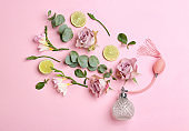 Beautiful flat lay composition with bottle of perfume, lime, eucalyptus and flowers