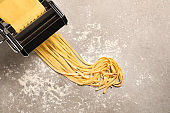 Pasta maker machine with dough on grey table