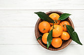 Fresh ripe tangerines with leaves and space for text on white wooden table