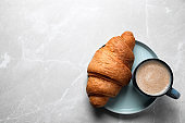 Fresh croissant and coffee on light grey marble table, top view