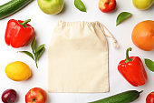Cotton eco bag, fruits and vegetables on white background, top view