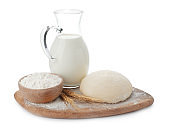 Board with dough, milk and flour on white background