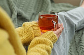 Woman with cup of tea sitting on plaid, closeup