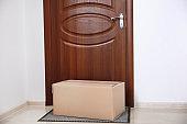 Cardboard box on rug near door. Parcel delivery service
