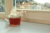 Cup of hot tea near window on rainy day.  Space for text