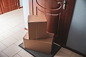 Cardboard boxes on rug near door. Parcel delivery service