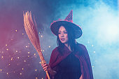 Portrait of beautiful young woman in witch halloween costume wear witches hat holding broom over spooky dark magic background - Halloween party art design