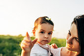 Closeup outdoor image of cute little girl embrace her mother on the field on the sunset sunlight. Mom and daughter playing on a flower field on nature and sky background.