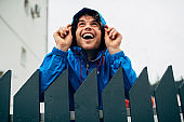 Outdoor image of happy man smiling broadly and wearing blue raincoat during rain. Handsome male in blue raincoat enjoying the rain next to the house. Young man has a joyful expression in rainy weather
